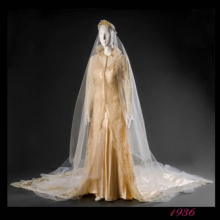 White wedding dress with lace overlay and long veil against grey backdrop
