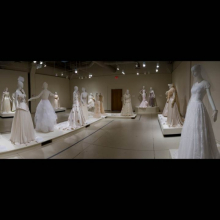 White gallery with several rows of contemporary wedding dresses on mannequins