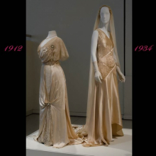 Two white wedding dresses dated 1912 and 1934 on mannequins on platform